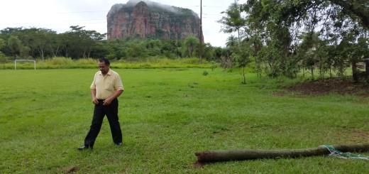 El director de la escuela muestra el poste caído.